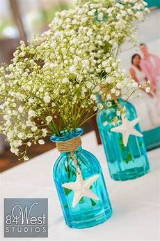 beautiful beach themed centerpiece using blue mason jars starfish and baby s breath perfect
