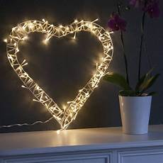 this beautiful heart wreath is decorated with soft white fairy lights around a pretty white