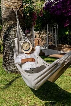 mann der in einer h 228 ngematte im garten sich entspannt