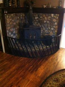 river rock stove surround half an old hay ring spray painted black as safety fence diy