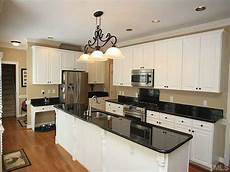 gorgeous kitchen combination of black granite countertops with white cabinets