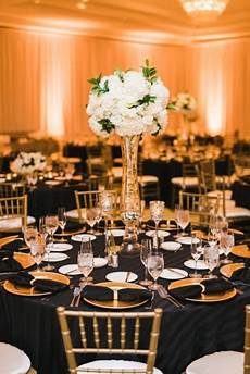 black gold and white wedding reception decor hydrangea centerpieces with black striped linens