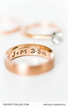 a gold engraved wedding ring with the couples initials and wedding date