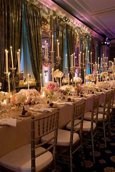 picture of formal wedding tables with white tablecloths long thin candles pink and white