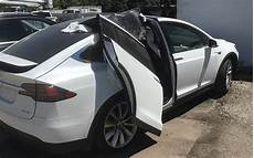 tesla model y doors tesla model x clipped one of its falcon wings on a garage