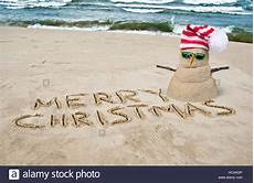 merry christmas in sand with snowman with hat 128076278 alamy