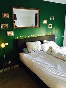 wand grün streichen schlafzimmer mit dunkelgr 252 ner wand und goldrahmenfotos