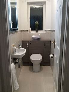 downstairs bathroom ideas small cloakroom grey lined wall and floor tiles edged with mosaic grey furniture surround with