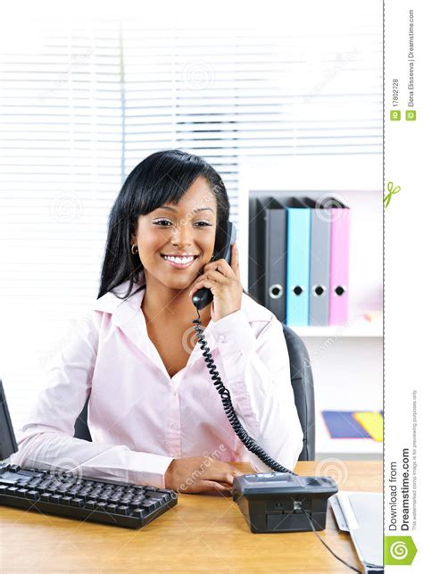 smiling black businesswoman on phone at desk stock photo