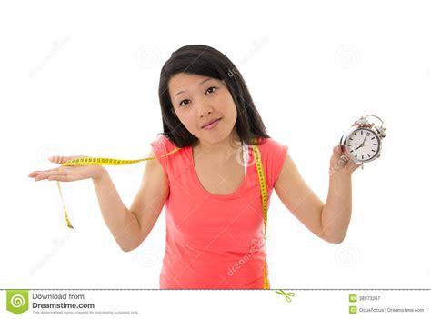 asian woman worried starting diet holding clock stock