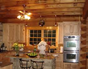 classy ceiling fan lights hang on wooden plafond over pine cabinetry set and marble island