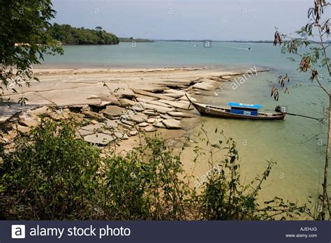 Rock The Boat En Francais by Traditional Longtail Boat At The Exposed Rock Plates Of