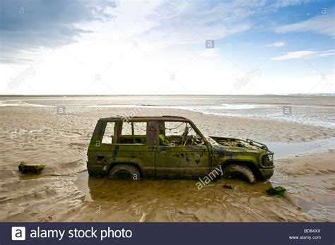 Abandoned Car Partially Buried In Sand Morecambe Bay Stock
