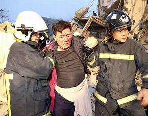 A rescue team help a victim to safety at a damaged ...
