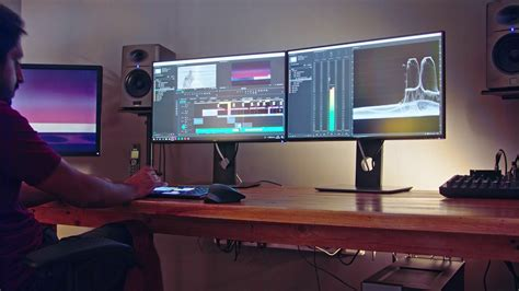 Video editor sitting in a dark editing suite working on a ...
