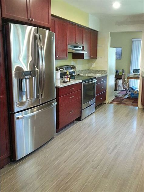 hardwood floors with cabinets grey hardwood floors accent a modern kitchen with cherry cabinets and stainless steel appliances