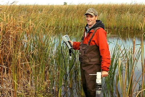 Research biologist Bryan Page is knee deep in wetlands ...