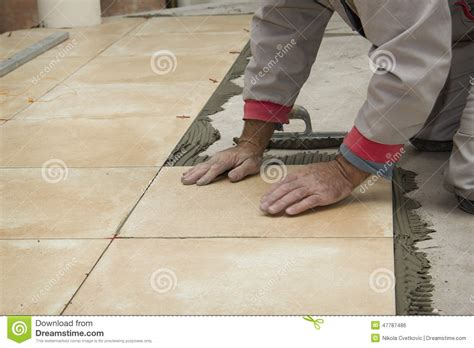 Regrouting Bathroom Tile Floor by Male Worker Tiling A Wall Royalty Free Stock Image