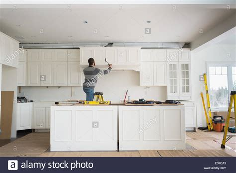 carpenter installing kitchen cabinet stock photo royalty