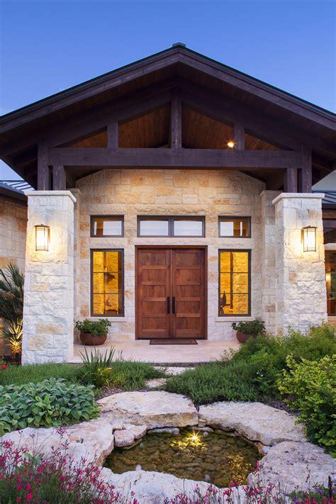 stone columns wood beam details  large windows add interest   front elevation