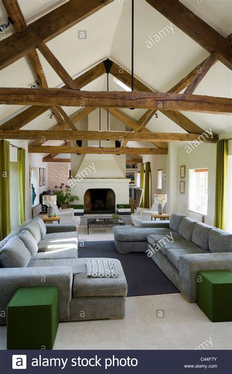 open plan barn conversion  beamed ceilings grey sofas