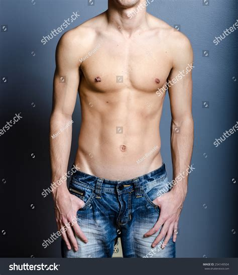 Male Ripped Body With Hands In Pockets And Nipple Piercing