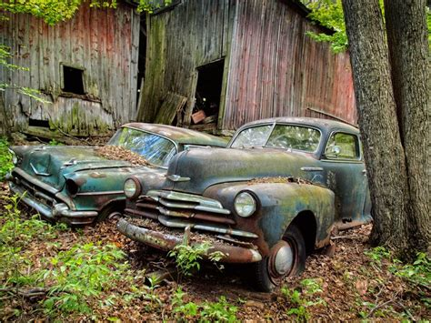 Abandoned Cars Behind A Delapidated Barn In Rural