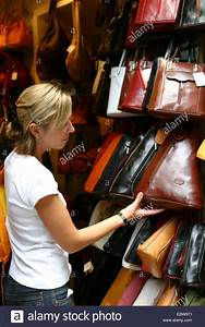 young woman looking at handbags in a leather goods store ...