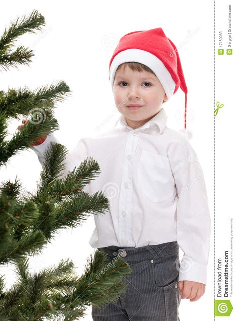toddler in christmas hat decorating new year tree stock