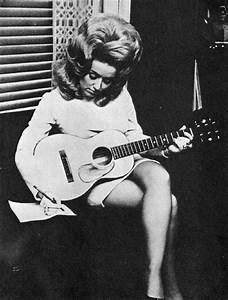 Young Dolly Parton sitting with a guitar writing a song ...