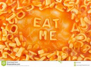 pasta shaped letters spelling eat me in tomato sauce stock With letter shaped pasta