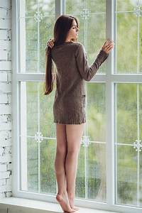 Beautiful young woman standing alone close to window with ...
