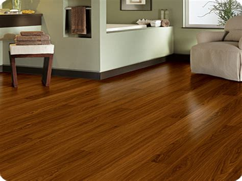 brown wooden vinyl plank flooring matched with olive wall plus black baseboard molding
