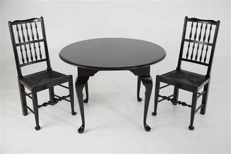black lacquer colonial revival style chairs and