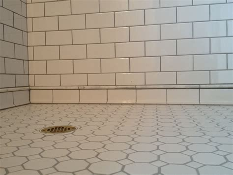 white subway tile shower with marble pencil trim detail in
