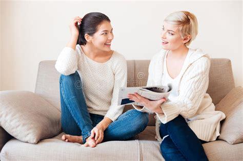 Zwei Frauen, Die Zeitschrift Auf Dem Sofa Lesen Stockfoto