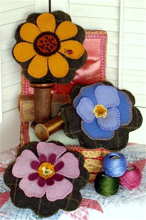 pretty wool applique flowers atop  stuffed pin cushion