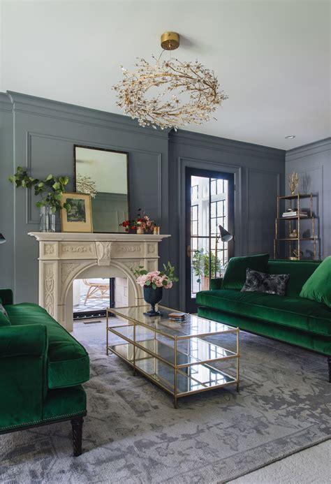 green sofas grey walls vertical mirror  fireplace