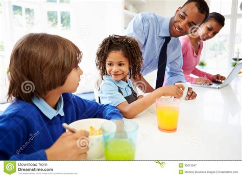 Family Having Breakfast In Kitchen Before School And Work Stock Image