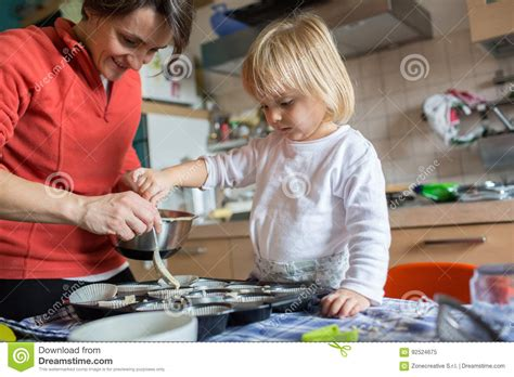 l amour dans la cuisine aide de fille de bébé faisant cuire avec sa maman dans la