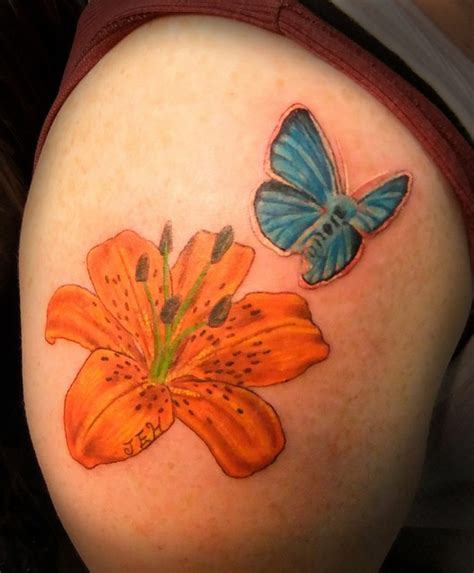 cute orange lily  blue butterfly flower tattoo