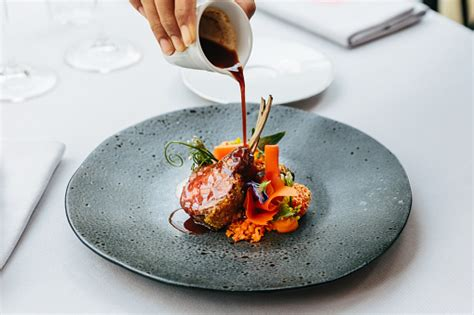 modern french cuisine roasted lamb neck rack served  carrot yellow curry pouring lamb sauce