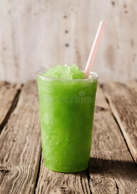 green slushie drink  plastic cup  straw stock photo