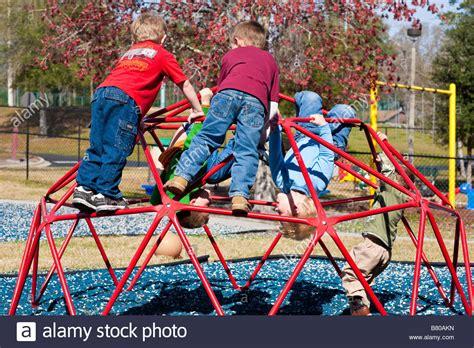 hanging on jungle stock photos amp hanging on jungle 831 | preschool boys playing on jungle gym playground equipment at preschool B80AKN