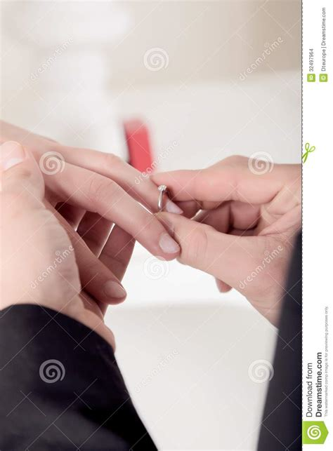 man slipping an engagement ring onto finger stock images image 32497964