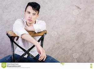 Man On Chair Against Wall Stock Photo - Image: 72196915