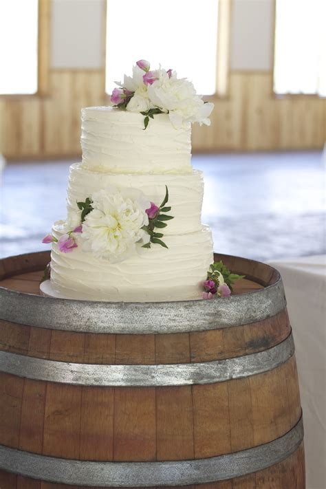 Rustic Wedding Cake With White And Pink Floral Wine