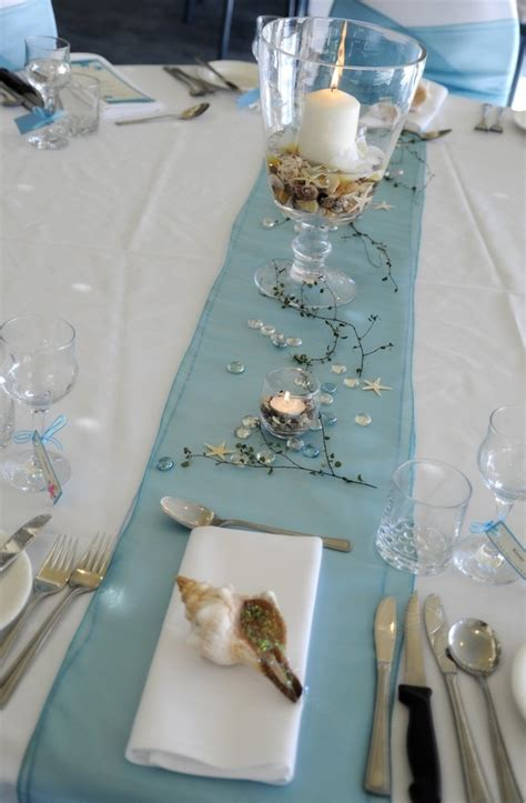 Picture Of a beach tablescape with a blue runner twigs