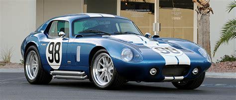 classic alfa romeo sedan driving the superformance shelby cobra daytona coupe