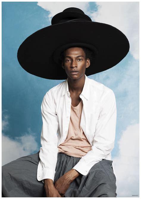 ty ogunkoya wears  big hat poses  snake